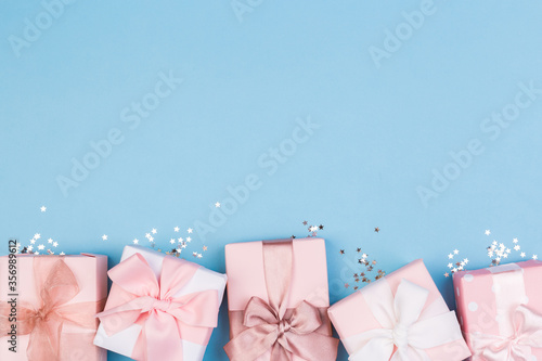 Gift or gift box and stars confetti on a blue table from above. Flat composition for birthday
