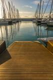 Marina with walkway and boats at sunset