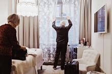 Senior Man Opening Curtains Wh...