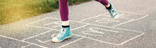 Closeup Of Child Girl Playing Jumping Hopscotch Outdoors. Funny Activity Game For Kids On Playground. Summer Street Sport For Children. Happy Childhood Lifestyle. Banner Header For Website.