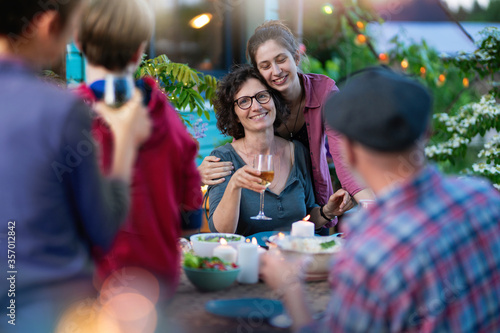 Foto In the evening, dinner with friends at a table in the garden, in front of the wooden house