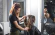 Profesional de peluquería trabajando, peinando, tiñendo y cortando cabello.