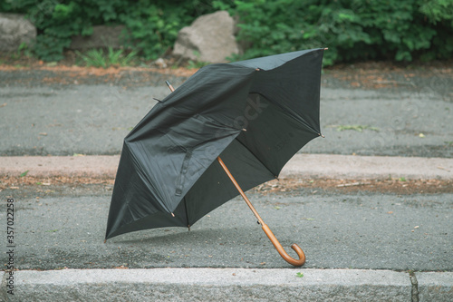 Broken umbrella thrown away and lying on the street. Fototapete