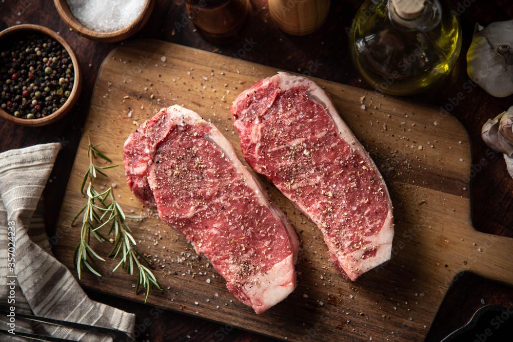 Fototapeta seasoned raw sirloin beef steak on cutting board