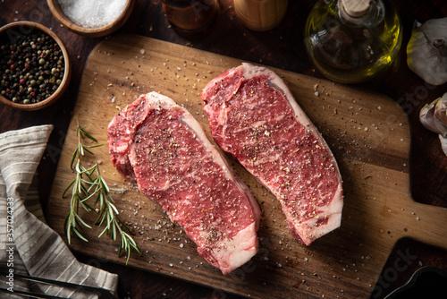 Obraz seasoned raw sirloin beef steak on cutting board - fototapety do salonu