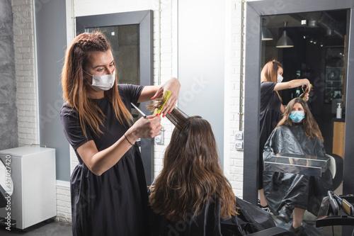 Fotomural Mujer estilista corta el pelo a mujer clienta, con la mascarilla puesta de prote