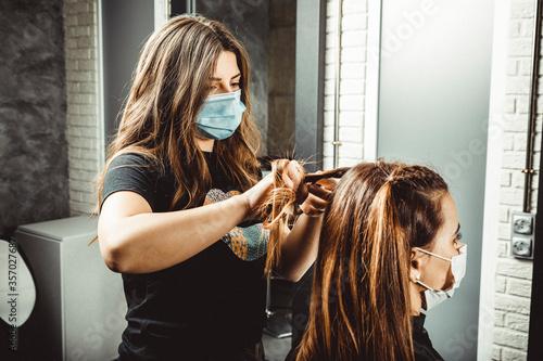 Cuadros en Lienzo Mujer estilista corta el pelo a mujer clienta, con la mascarilla puesta de prote