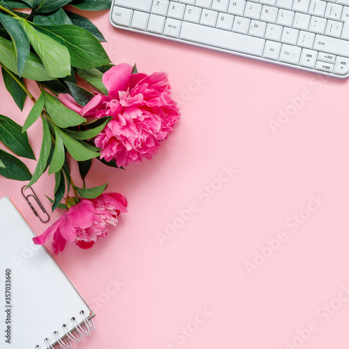 Fototapeta Laptop, accessories and bouquet of beautiful peonies on pink background. Flat lay of working place. obraz
