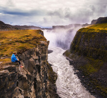 Hiker Sitting At The Edge Of The Gullfoss Waterfall In Iceland