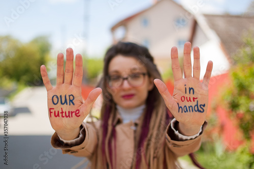 Modern girl with long dreadlocks and eyeglasses in nude color trench is showing hands with written slogan 'Our future in our hands' on some building background Tapéta, Fotótapéta