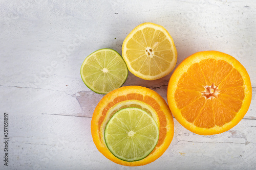 Verity of halved citrus fruit oranges lemons and limes flat lay on a  vintage wood background