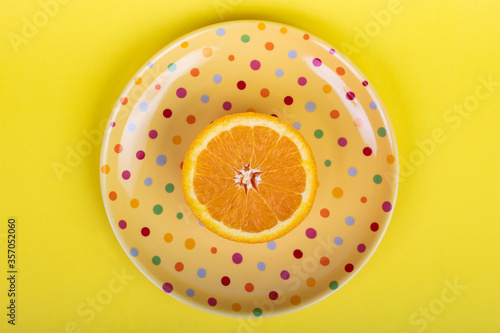 One halved orange on polka dot serving plate on a bright yellow flat lay background