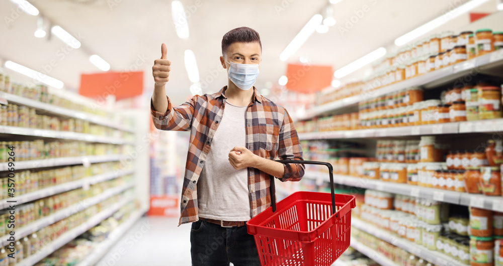 Fototapeta Guy in a supermarket with a protective mask and a shopping basket showing thumbs up