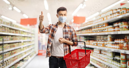 Fotografía Guy in a supermarket with a protective mask and a shopping basket showing thumbs