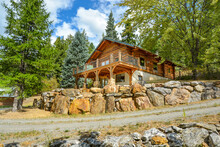 A Picturesque Rustic Log Home In The Mountains Surrounded By Pine Trees On A Rocky Hillside In Coeur D'Alene, Idaho.