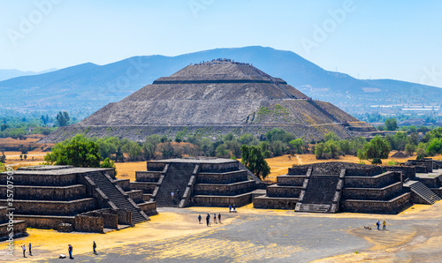 The majestic Sun Pyramid with a few unrecognizable tourists and minor temples in Teotihuacan, Mexico City, Mexico.