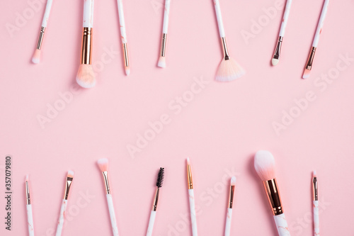 Frame of makeup brushes on pink background. Beauty salon banner mockup. Flat lay, top view.
