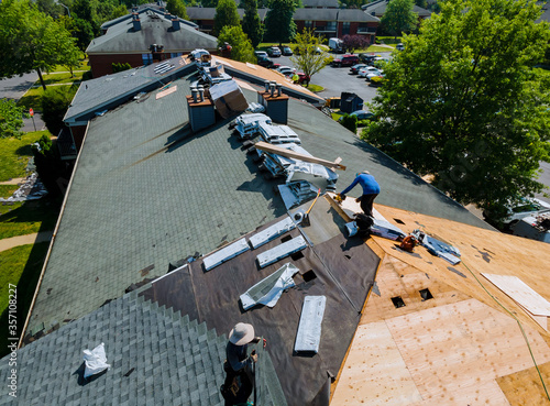 Fototapeta Construction worker on renovation roof the house installed new shingles