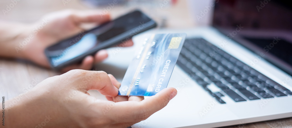 Fototapeta woman hand holding credit card with using smartphone and laptop for online shopping while making orders at home. business, lifestyle, technology, ecommerce, digital banking and online payment concept