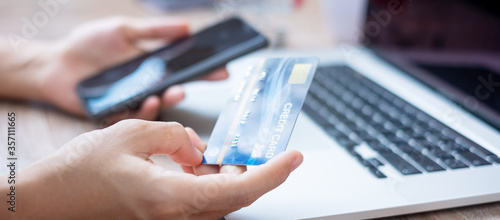 Obraz woman hand holding credit card with using smartphone and laptop for online shopping while making orders at home. business, lifestyle, technology, ecommerce, digital banking and online payment concept - fototapety do salonu