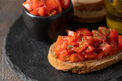 Fototapeta Crusty Italian appetizers, bruschetta slices of toasted baguette with tomato, basil and olive oil obraz
