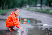 Girl Plays In Paper Boats In A Puddle / Autumn Walk In The Park, A Child Plays In The Rain