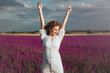 Beautiful girl in white dress is laughing on summer field of lavender