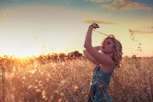 Fototapeta beautiful blonde girl with heavenly dress at sunset in wheat field