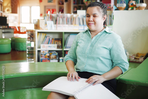 Tablou Canvas Portrait of Asian young blind person woman disabled people reading Braille book studying in creative library