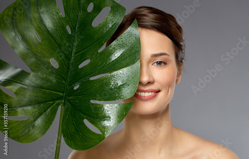 beauty, bodycare and people concept - beautiful young woman with green monstera Fototapet