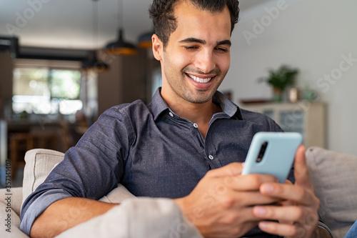 Leinwand Poster Latin man using smartphone at home