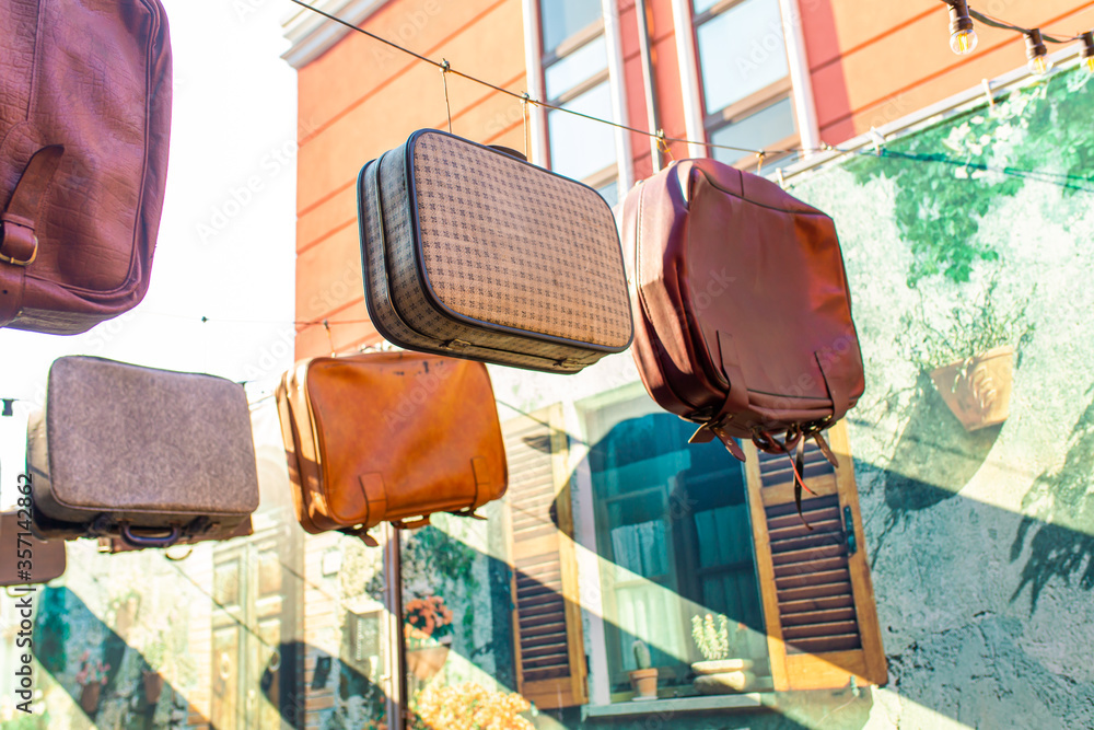 Old bags and suitcases are hanging in the sky. Exterior design of a thematic institution. Bag shop.