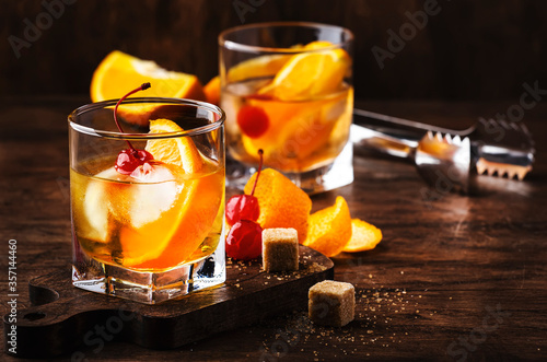 Old fashioned cocktail with bourbon, cane sugar, orange slice, cherry and orange peel garnish, vintage wood table, copy space
