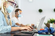Young people working in co-working creative space wearing surgical mask protection for preventing corona virus spread - Social distancing, content creator startups and technology concept