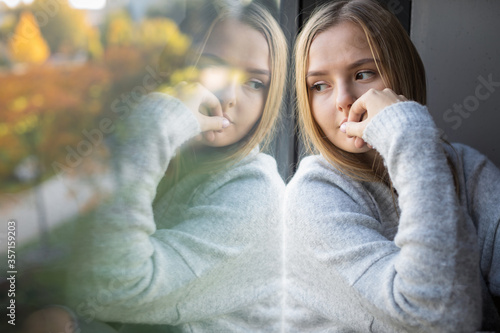 Photo Depressed/anxious young woman sitting by a large window, feeling blue, sad, unce