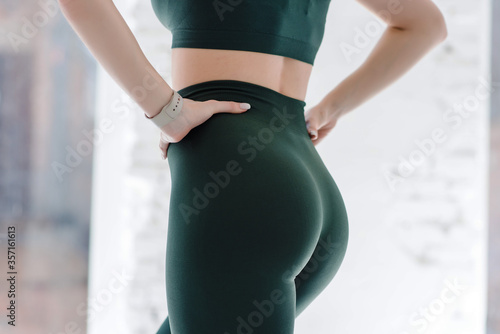 Obraz Cropped close up view photo of sexual sporty sportive tempting beautiful attractive nice round ass wearing green tight pants leggings - fototapety do salonu