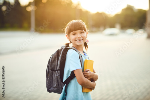 A schoolgirl with a backpack and books stands on a city street Fototapeta