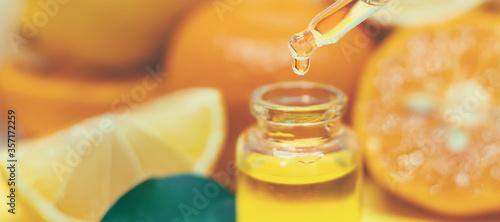 Fototapeta orange essential oil on a yellow background. Selective focus. obraz
