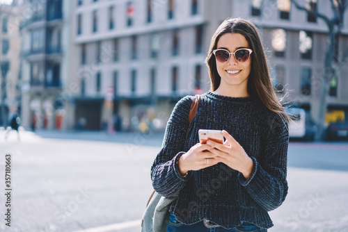 Portrait of cheerful brunette hipster girl in sunglasses walking in downtown on sunny weather Fototapete