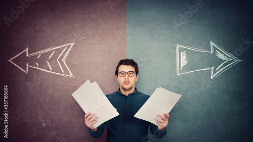Perplexed businessman has to choose as holds different paper documents in both hands Fotobehang