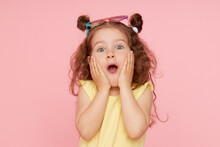 Portrait Of A Happy Child. Cute Little Girl With A Funny Face On A Pink Background. Advertising Baby Products