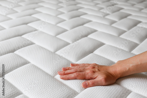Cropped shot of young woman's hand testing white orthopedic matress on firmness Fototapeta