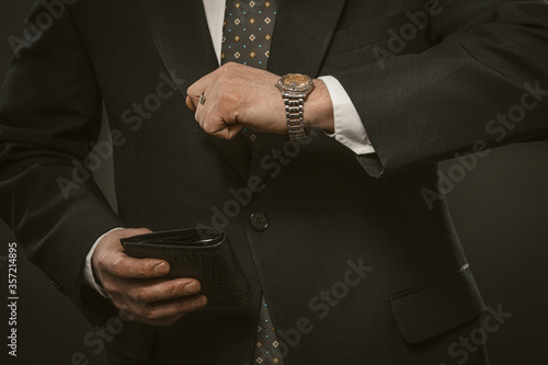 Fototapety, obrazy: Businessman checks time looking at wristwatch holding expensive leather wallet in his hand. Close up shot. Deadline concept. Toned image.