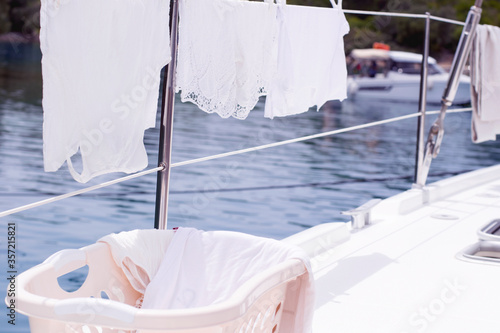 Photo Laundry day on sailing boat, white clothes hanging on board line in sunlight