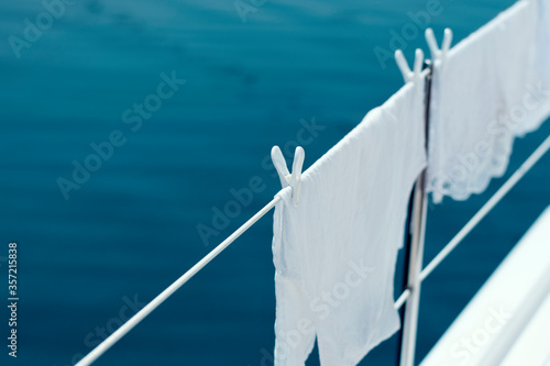 Photo White laundry on line, clothes on board in sunlight