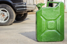 Green Jerry Can Close-up On Blurred Background Of Black Car