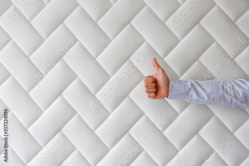 Cropped shot of man's hand showing thumbs up over white orthopedic mattress pattern Fototapeta