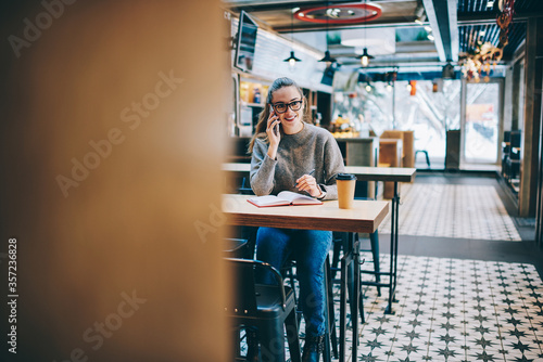 Foto Happy hipster girl sitting at cafeteria table with textbook