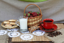 On The Table Is A Basket With Strawberries, A Cup Of Coffee, Coffee Beans, Cinnamon Sticks, A Cup Of Milk And A Plate Of Cookies.