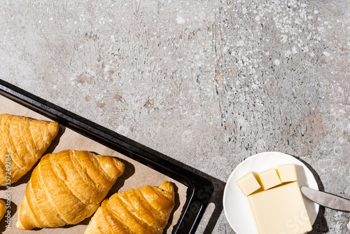 Fototapeta top view of baked delicious croissants on baking tray near butter on concrete grey surface obraz